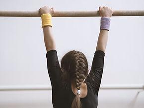 Gymnaste sur une barre en bois
