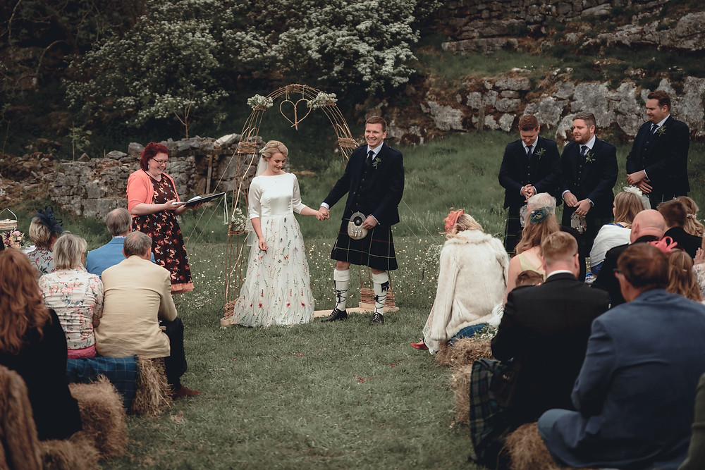 outdoor humanist wedding in a farmer's field. bride, groom, celebrant and guests share a joke