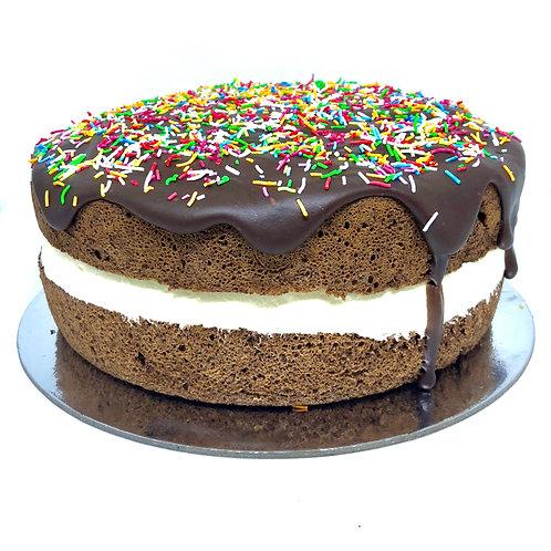 Gluten free chocolate sponge with cream, ganache and coloured sprinkles