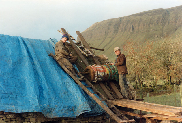 """Rolls of sod called """"scraws"""" are cut and rolled out on the roof. The thatch is pegged into this using twisted hazel rods called """"scallops."""" The old man Bertie Munns taught me how to make the traditional Irish thatched roof."""