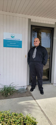 Francis Bugarin L.Ac. standing beside the entrance of Uyayi Acupuncture & Herbal Medicine Clinic