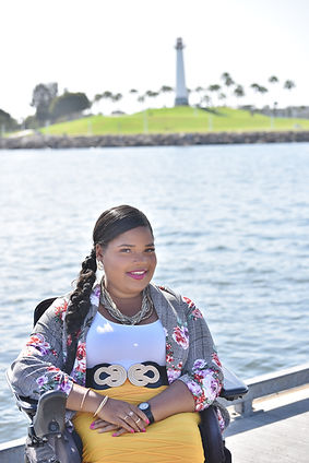 An African American woman sitting in a wheelchair in a floral blazer, white top and yellow skirt Her background is a body of water and a lighthouse on an island of grass.                                                                                                                                                                                                                                                                                                                                                                                                                                                                         nn                                                                                       An African american woman sitting in a wheelchair. Background is a body of water and a lighthouse surrounded by grass and trees.