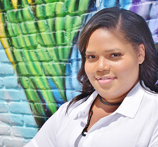 A headshot style photo of an african american woman behind a colorful blue and green background. She is wearing a white collared shirt and black necklace.