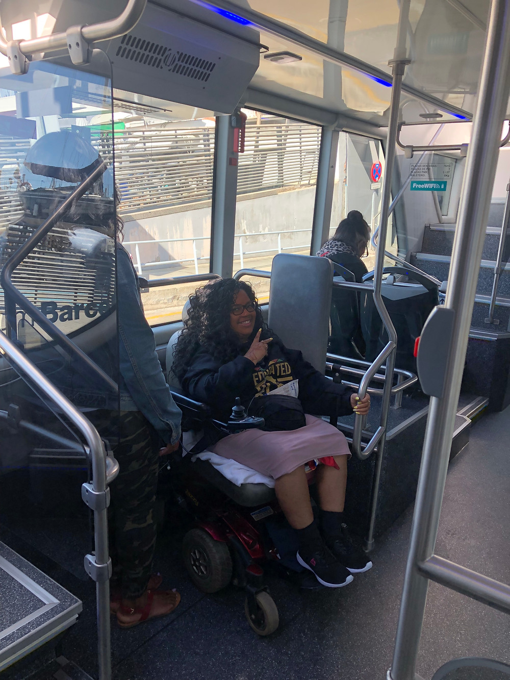 African American woman sitting in an electric wheelchair on a bus, holding on to the handle bar