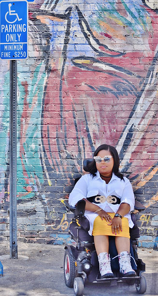 An African American woman sitting in a wheelchair weating a white collard shirt and yellow shirt. There is a disabled parking sign on her left hand side and her background is a multi-painted brick wall