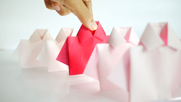 hand-selecting-one-red-among-white-origami-shirt-paper.jpg