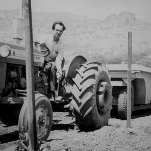 Warren Winiarski on tractor with his son in the background
