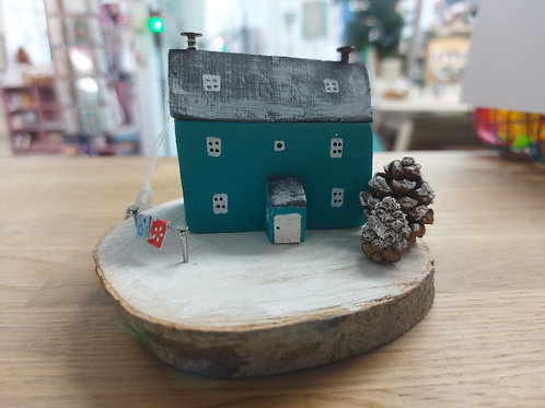 Teal seaside house made from local driftwood