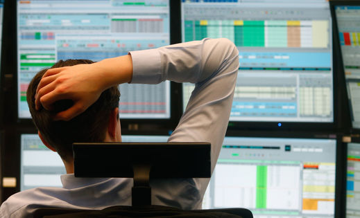 A financial trader monitors data on comp