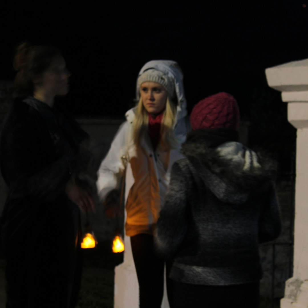 Tourists listen to their guide tell a ghost story on the streets of Punta Arenas, Chile