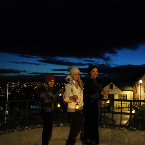 A small group poses at a lookout over Punta Arenas on their nocturnal ghost tour.
