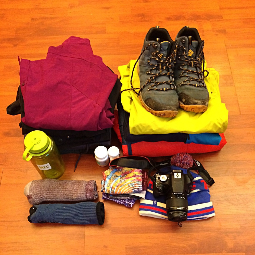Pile of folded outdoor clothes and shoes to pack for a vacation to Patagonia, Chile.