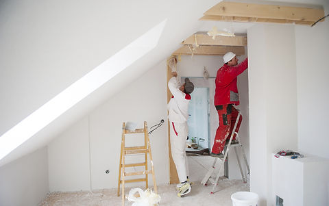 Construction worker is painting the wall in new house.jpg