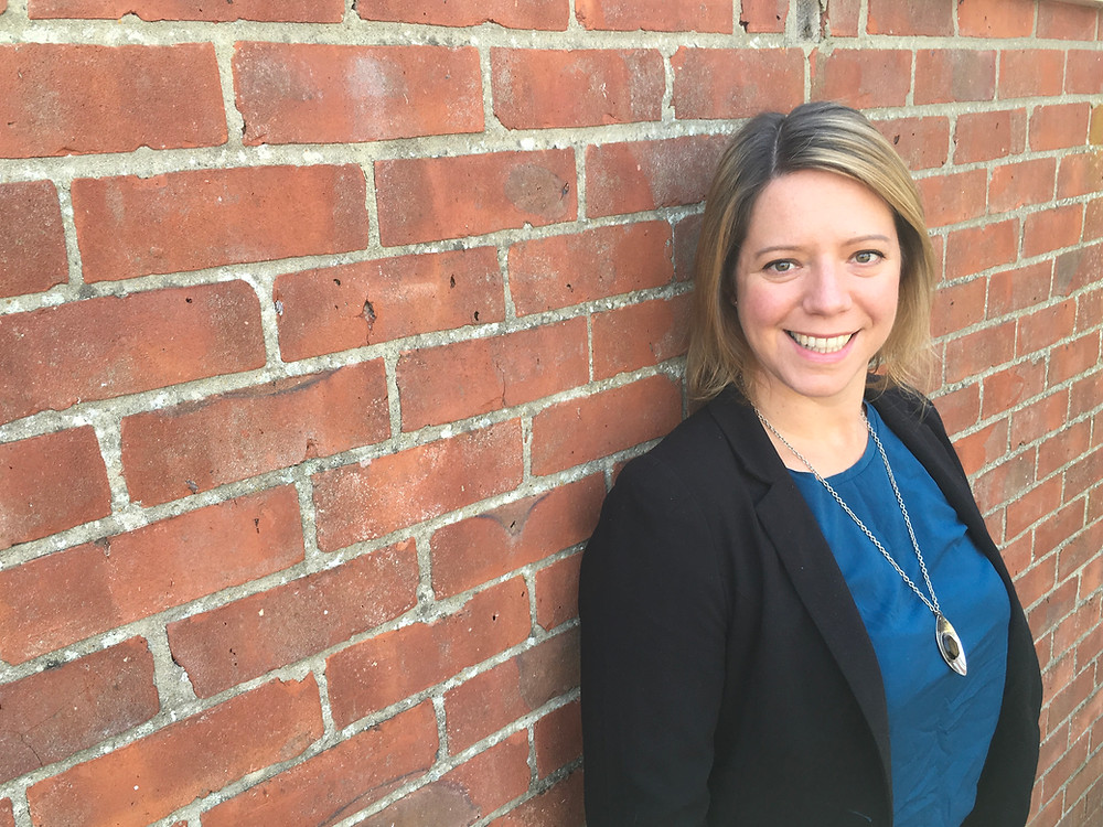 Photo of Samantha standing agains a brick wall.