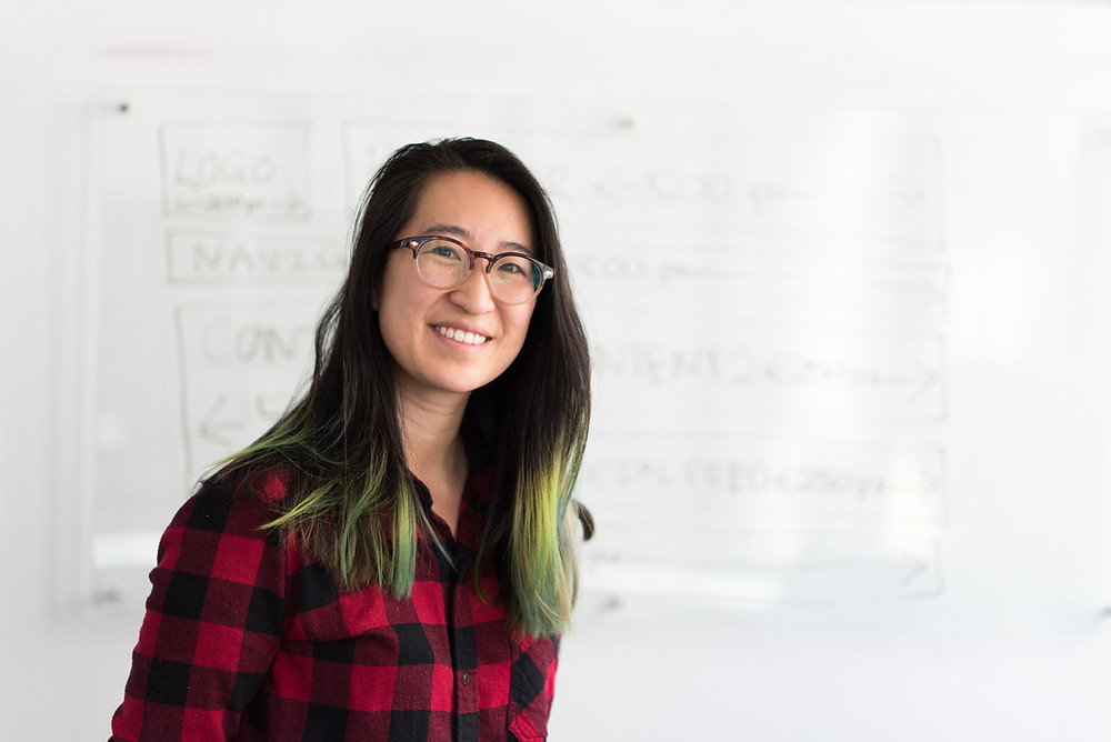 Women in red checked shirt looking confidently at the camera. She stands in front of a white board. She has long dark straight hair with dyed green ends.