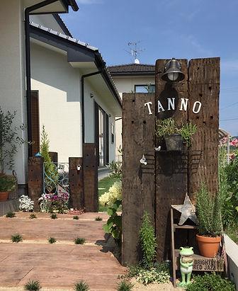 門柱はナチュラルガーデンを代表する枕木で。枕木の門柱にアイアンのサインをWhiteのエイジング塗装を施し、優しい雰囲気のアーチ型に設置。 アプローチは枕木調のスタンプコンクリート。目地にはタマリュウを合わせました。  明るく笑い声がたくさん聞こえてきそうな家族が浮かぶ門構えを作りたくて!