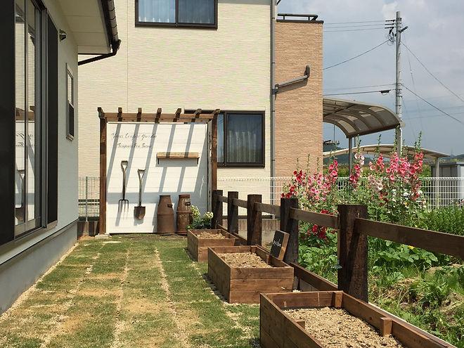 枕木のゲートをくぐると芝生の広がるプライベート空間。芝生の中には家庭菜園をしたいというT様のご希望で木製のポタジェを作りました。