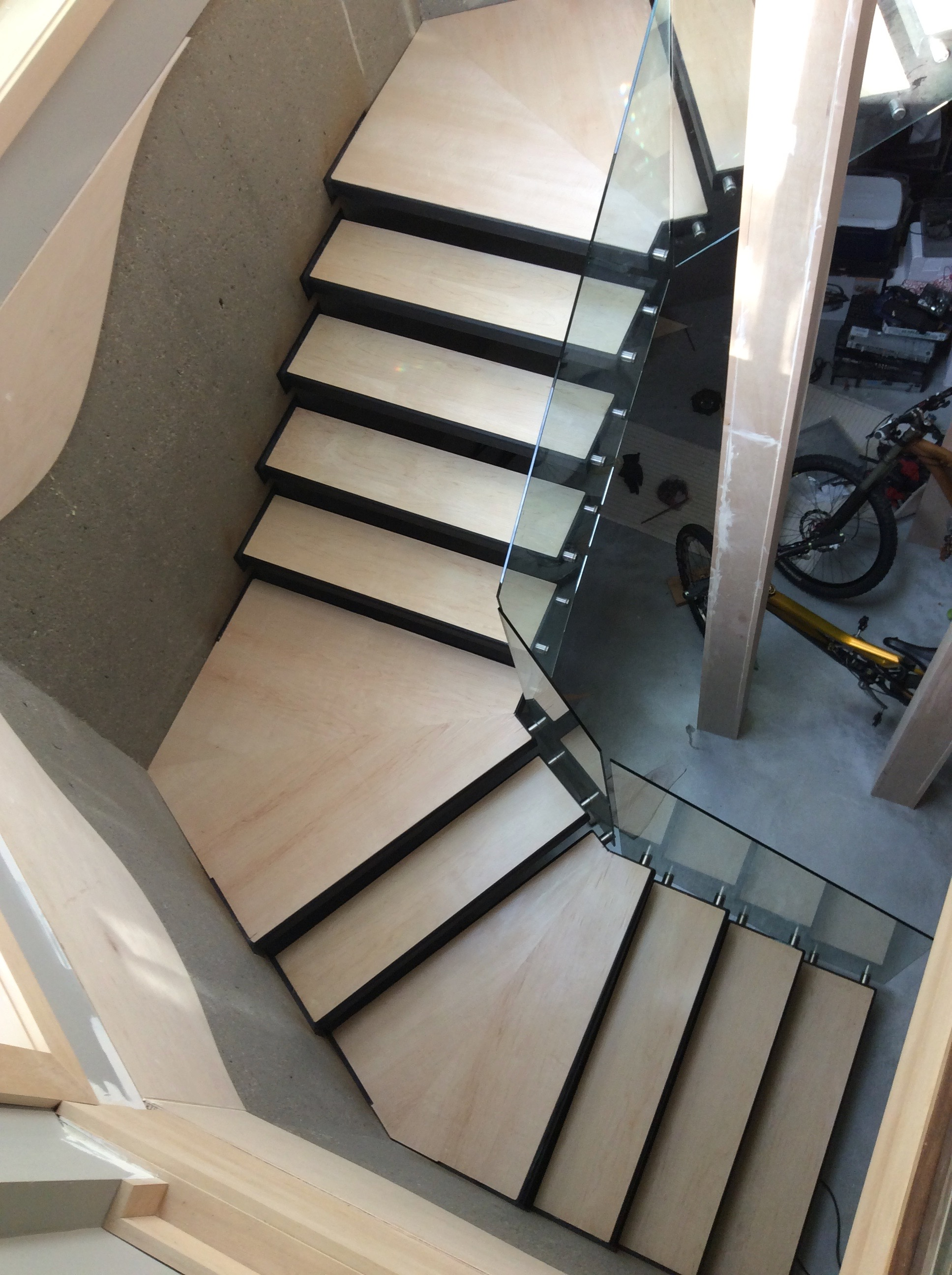Steel cantilevered basement stairs covered with Maple treads