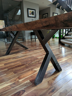 Live edge clara walnut dining room table with custom steel legs built specifically for the shape of