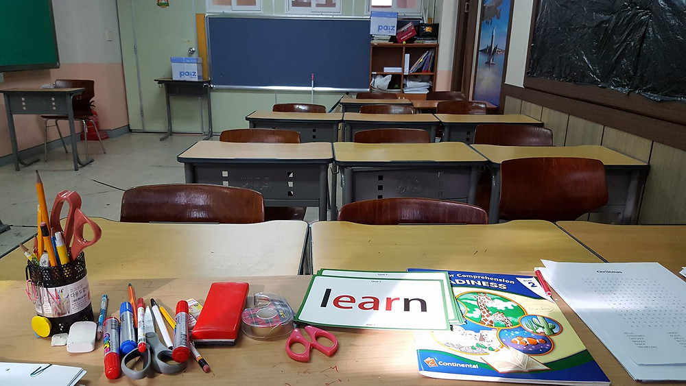 An empty classroom with English teaching materials on a teacher's desk.