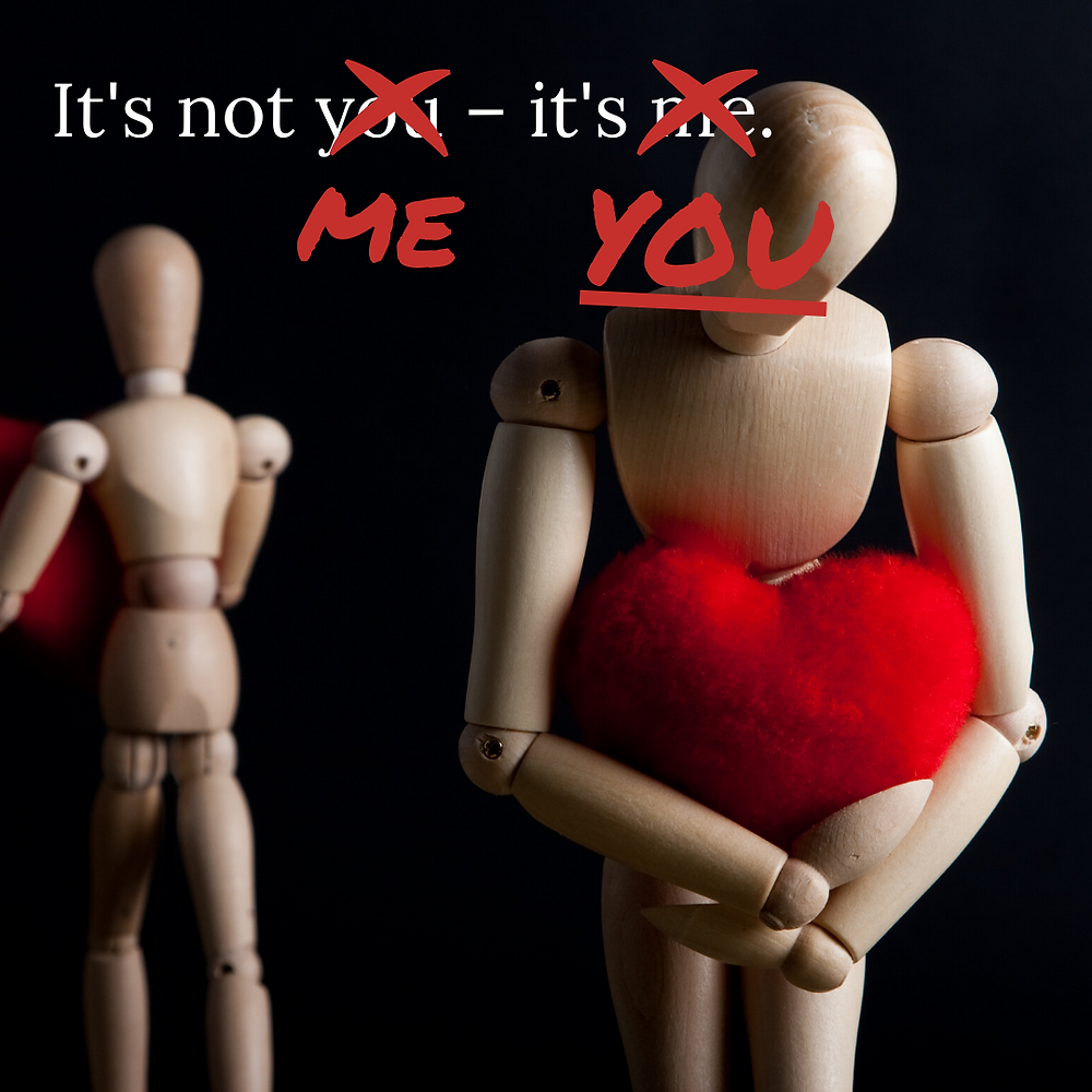 """""""It's not you, it's mean"""" has been altered to """"It's not me, it's you"""" two mannequins breaking up, one holding a red, fluffy heart."""