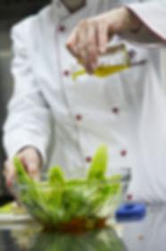 A chef dressing a salad