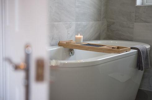 sensual candlelit bathroom with grey tiles