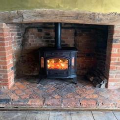 rustic log burner on a brickwork hearth
