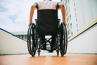 Person in a wheelchair outside, approaching an apartment complex.
