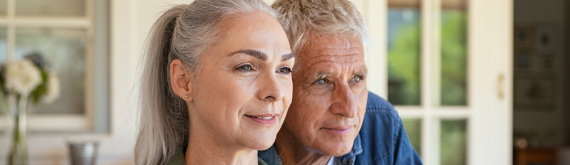 A senior couple on their front porch looking forward