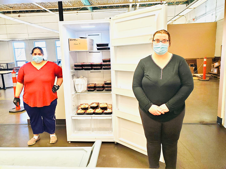 Two ladies standing in front of a new upright freezer donated to Imaginability from Enabling Access