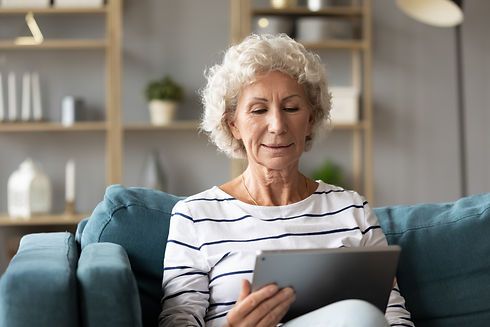 Calm mature woman using computer tablet, looking at screen, sitting on couch at home