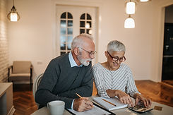 A happy senior couple sitting at their dining room table calculating finances