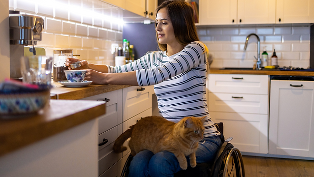 Woman with wheelchair in her accessible kitchen making tea with a cat on her lap