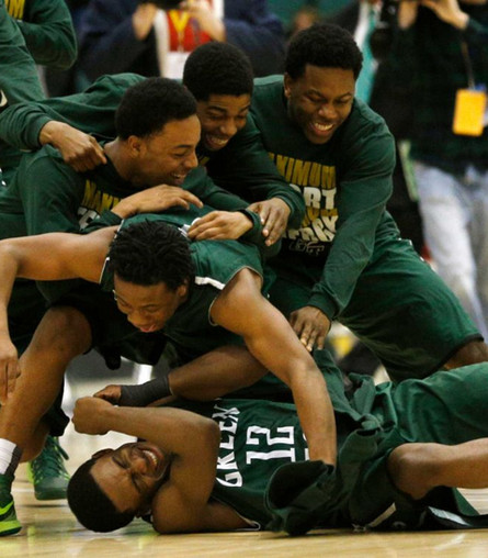 Green Tech players piled together on the floor in