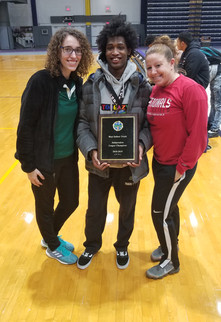 Track team member, track coach, and friend posing with celebratory plaque