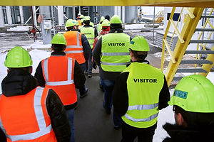 Group of people wearing safety gear walk through warehouse