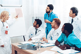 four healthcare professionals looking at a white board