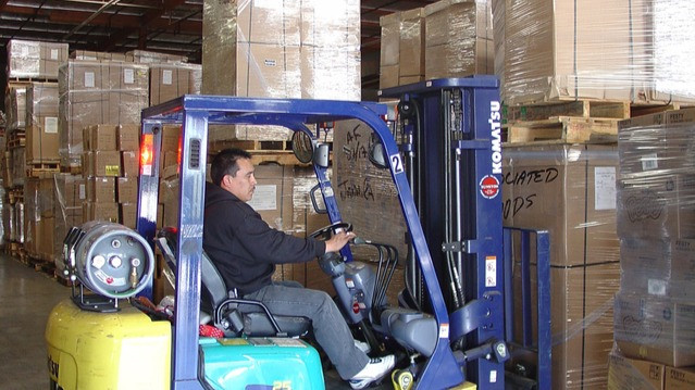 Man on a front loader loading boxes in warehouse