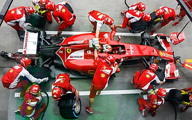 maintenance team wearing red changing tires for red racecar