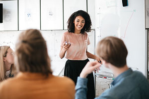 Woman standing in front of white board leading group discussion