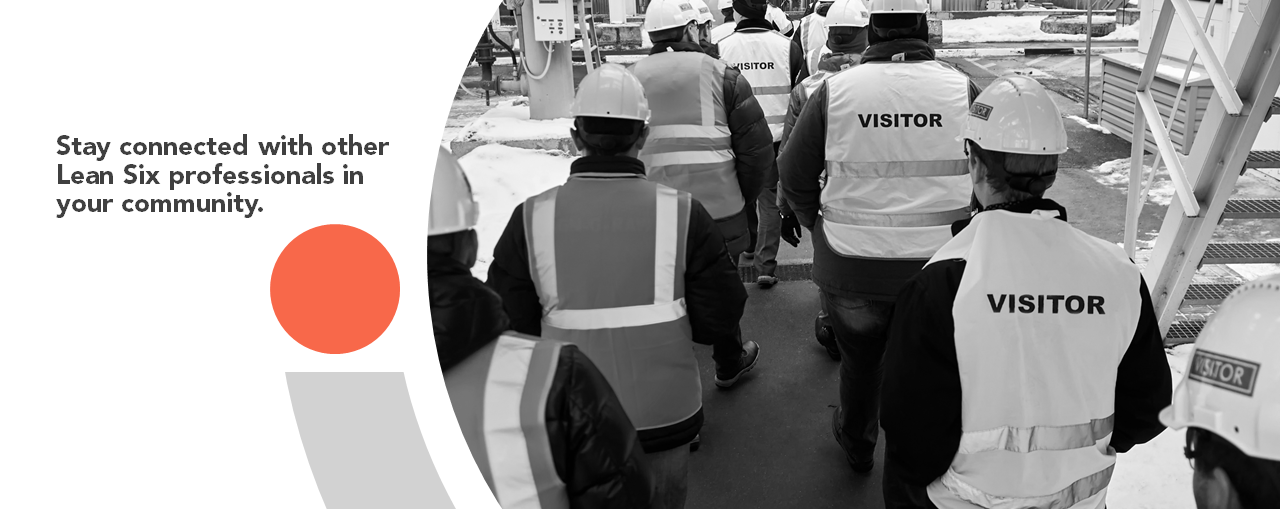 Group of people in safety gear touring a warehouse