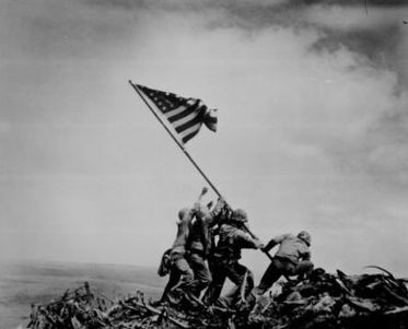 5 Marines and a Nvy Corpsman raise the American Flag over Mt. Suribachi during WW2