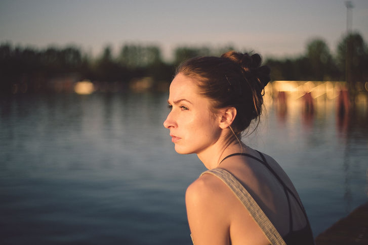 Woman at edge of water looking into sun