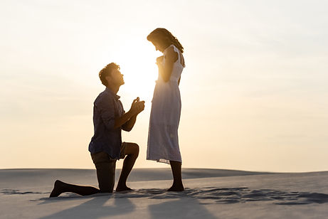 side view of young man doing marriage proposal to girlfriend on sandy beach at sunset.jpg
