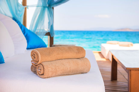 Set of rolled beach towels laying on a white couch in a luxury hotel cabana near the sea.j