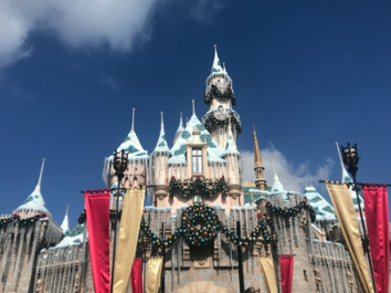 Picture of a Disneyland castle, adorned in wreaths and red and gold decorations for Christmas