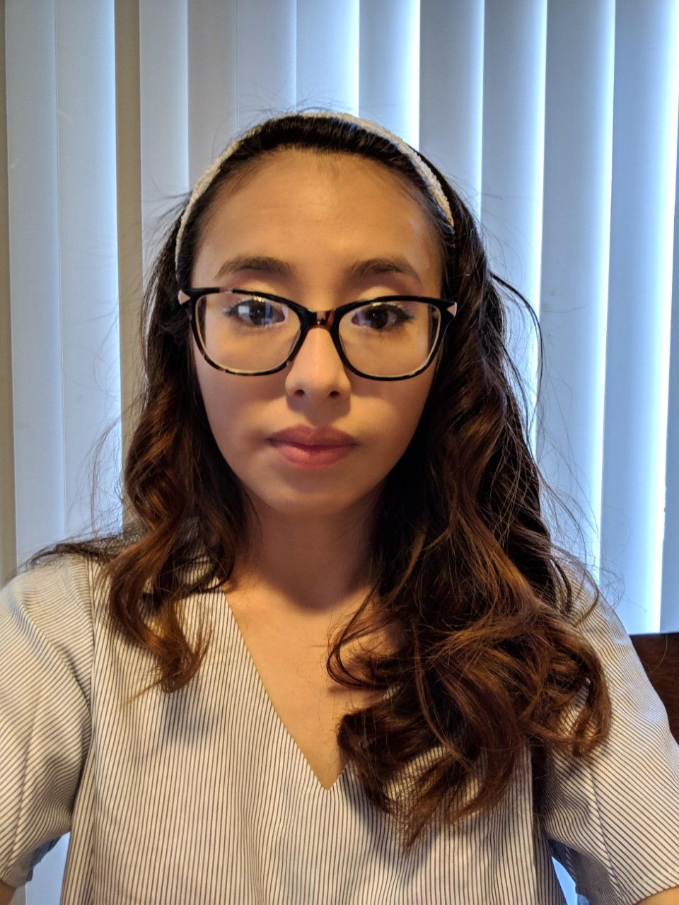 Picture of Kimberly, a young woman, wearing glasses, staring at camera