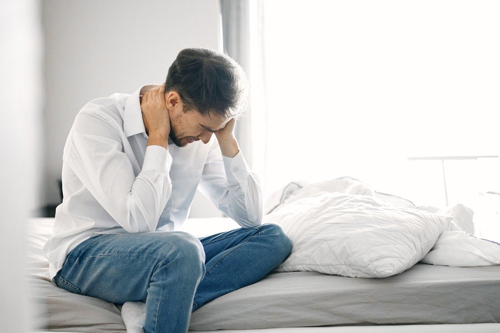 Man on bed with chronic pain