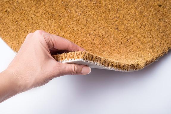 hand-holding-brown-doormat-carpet-textur